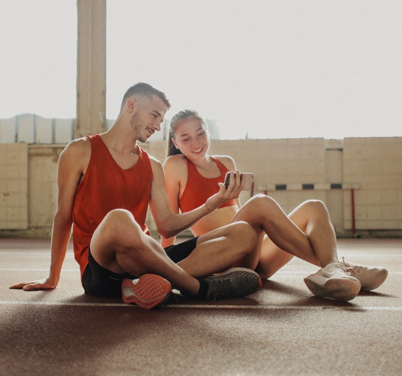 man and woman watching a workout video on a mobile phone