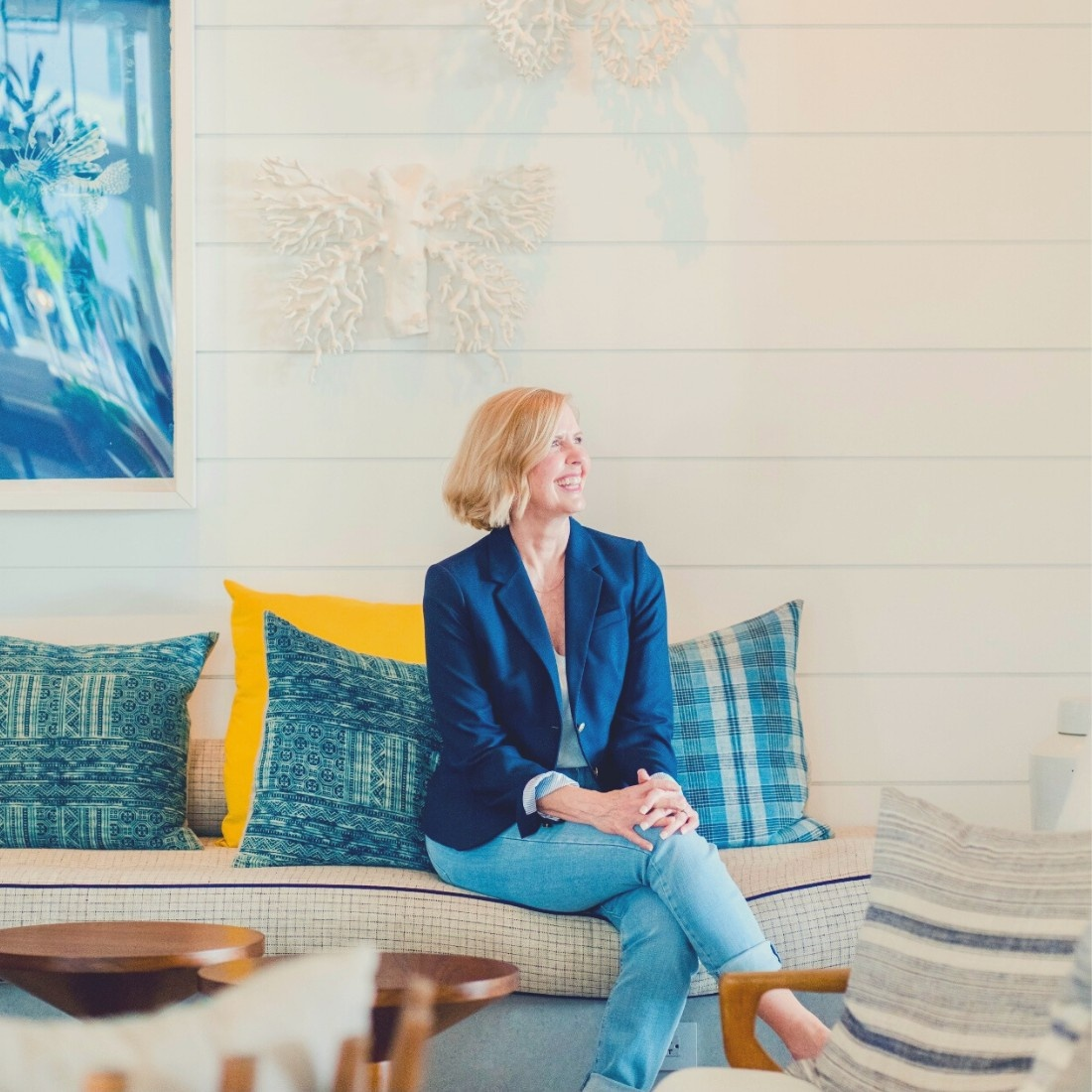 blonde woman sitting on couch with navy blazer and hands folded on her legs