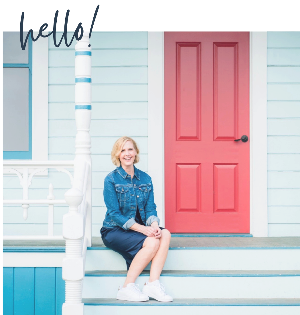 Blond woman sitting on porch with red door behind her
