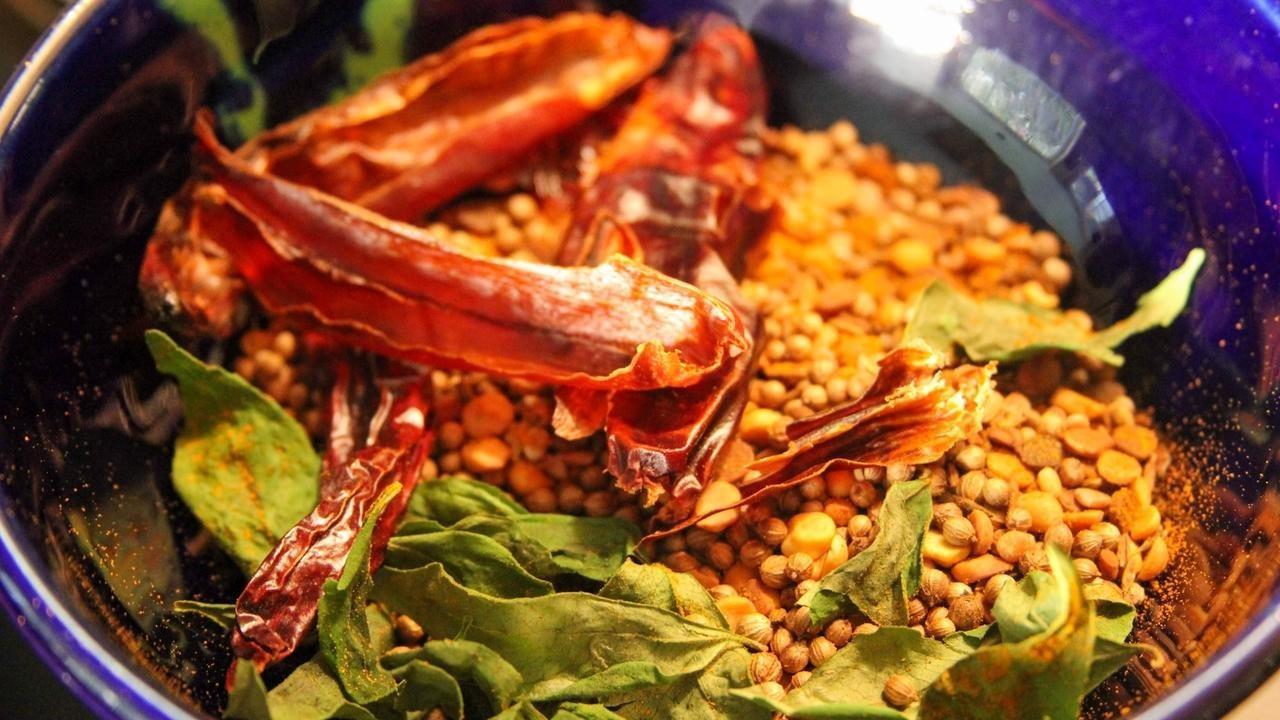 sambar masala recipe whole spices roasting in a pan