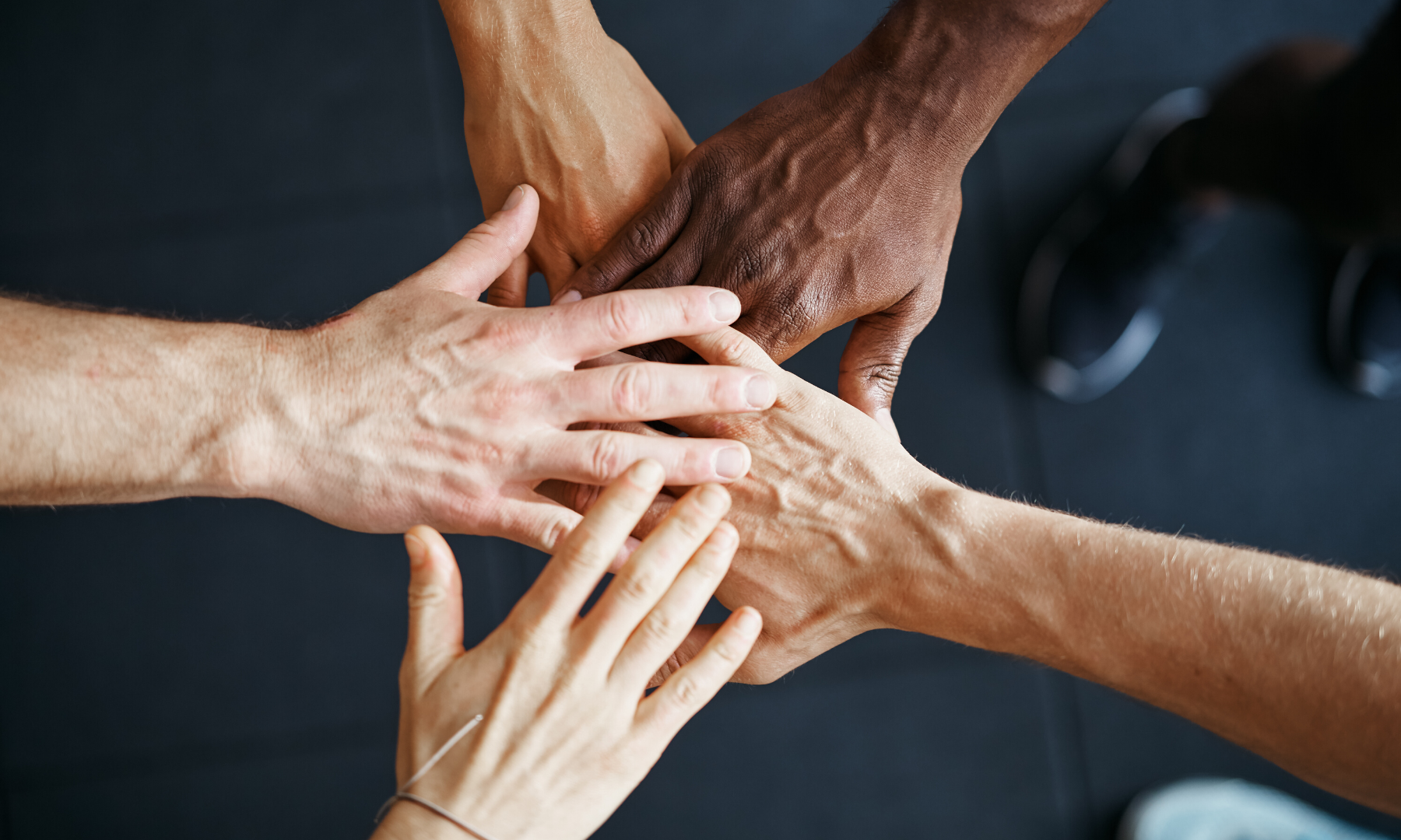 Five hands of different skin colour holding together as a team