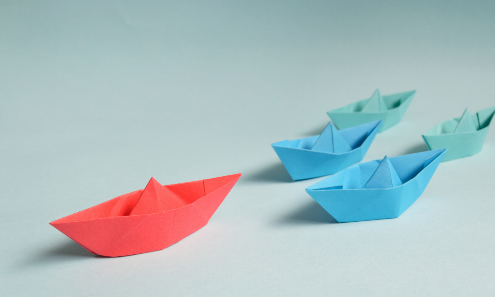 A red paper boat leading the way followed by blue smaller ships