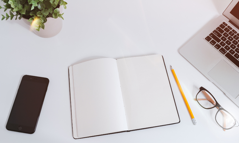 A blank notebook on a desk with a smartphone, pencil and glasses next to it