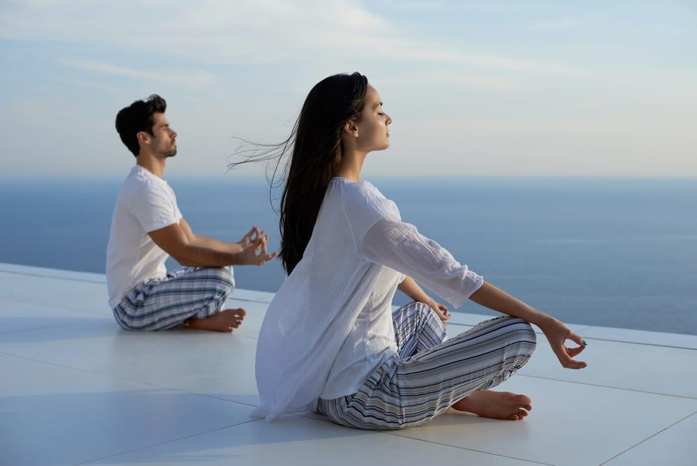 Man and woman seated meditating outside