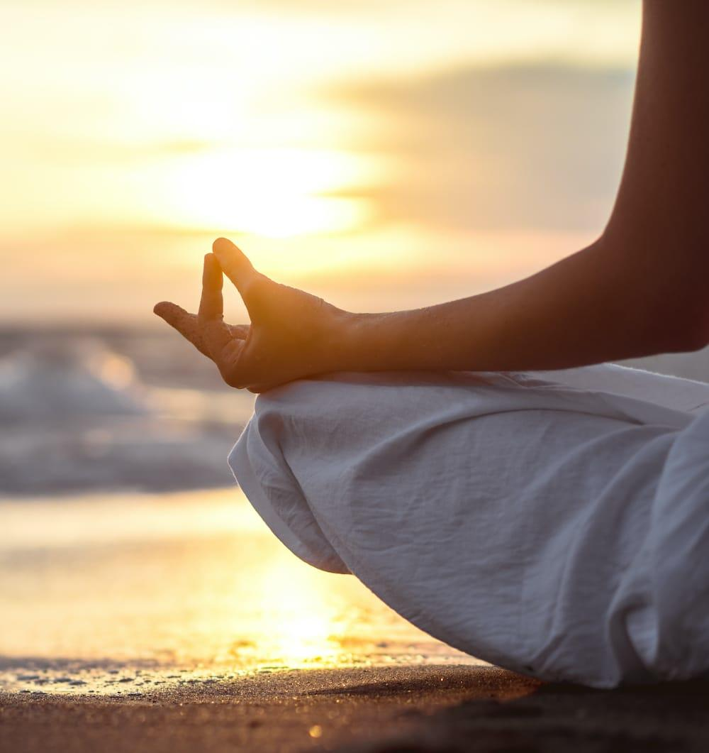 Person meditating on beach at sunrise