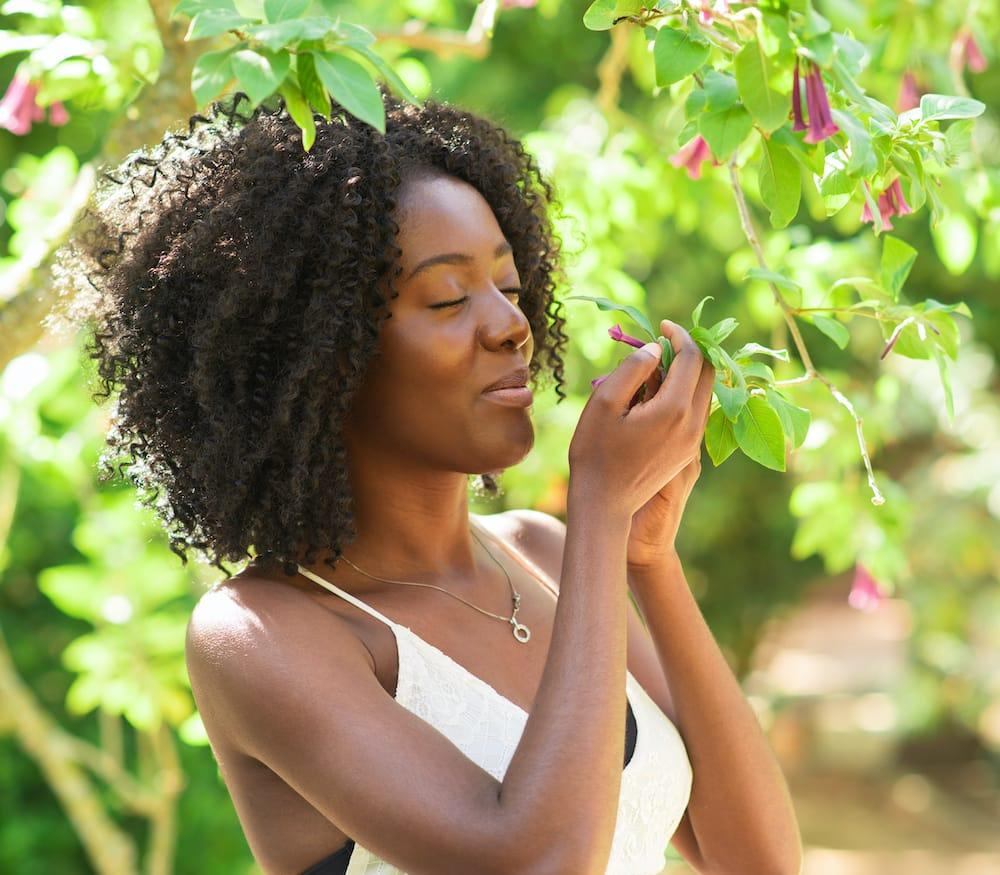 happy black woman smelling flowers