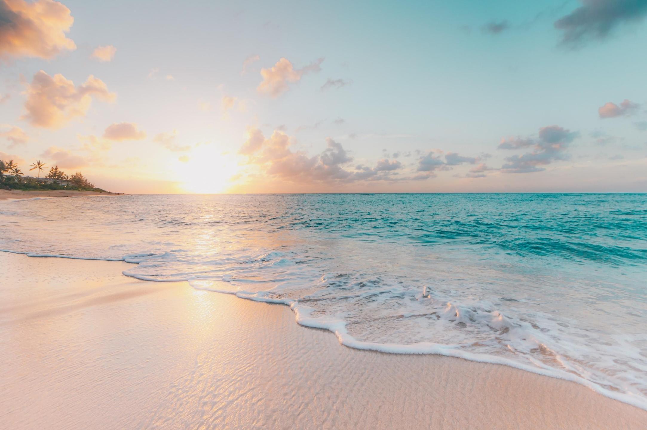 Sun shining over calm beach waves