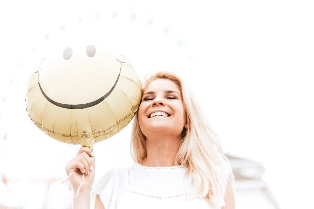 Smiling blonde white woman holding a smiley face balloon