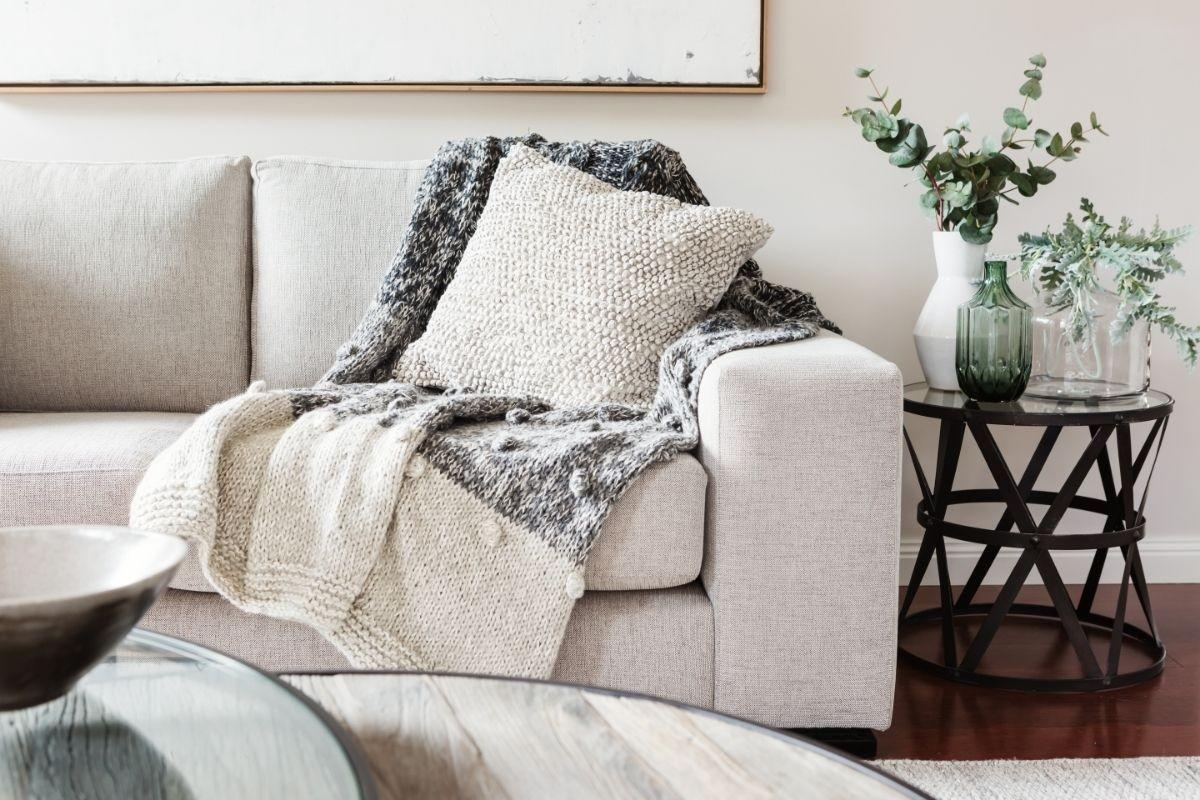 gray couch in a beautiful living room with a side table and vases