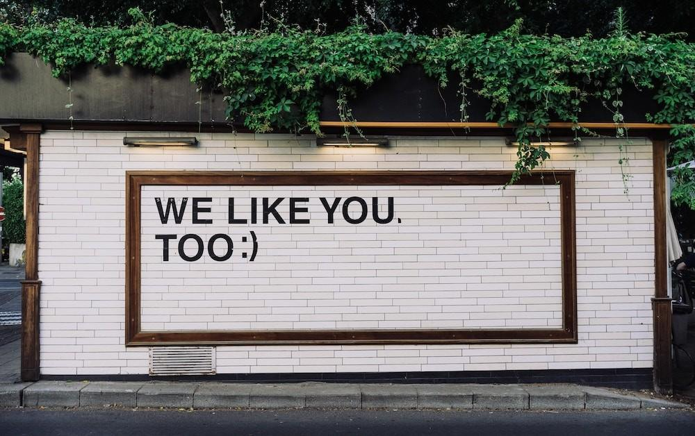 Brick wall painted with the words: We Like You, Too :)