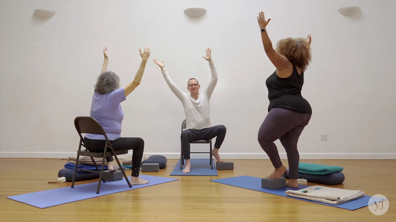 Photo of Jivana Heyman leading an Accessible Yoga class with two students. They are practicing tree pose with Jivana and one student in chairs and another student standing.
