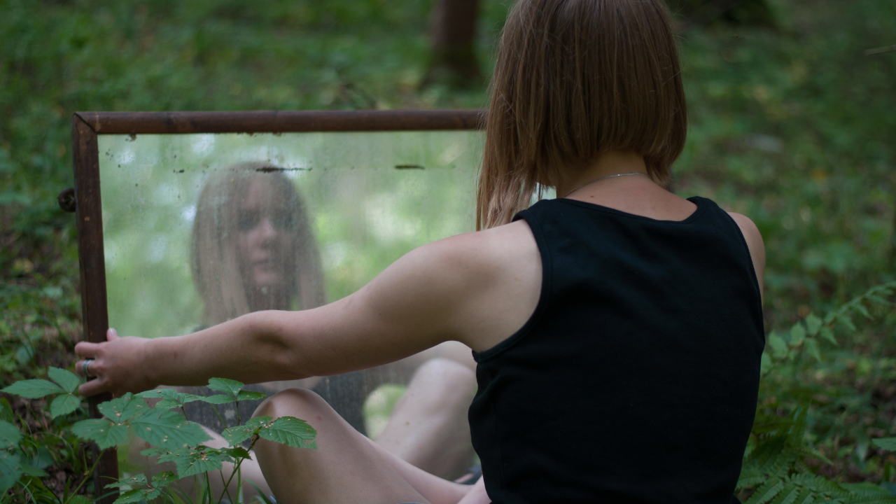 woman sitting in the forest looking in