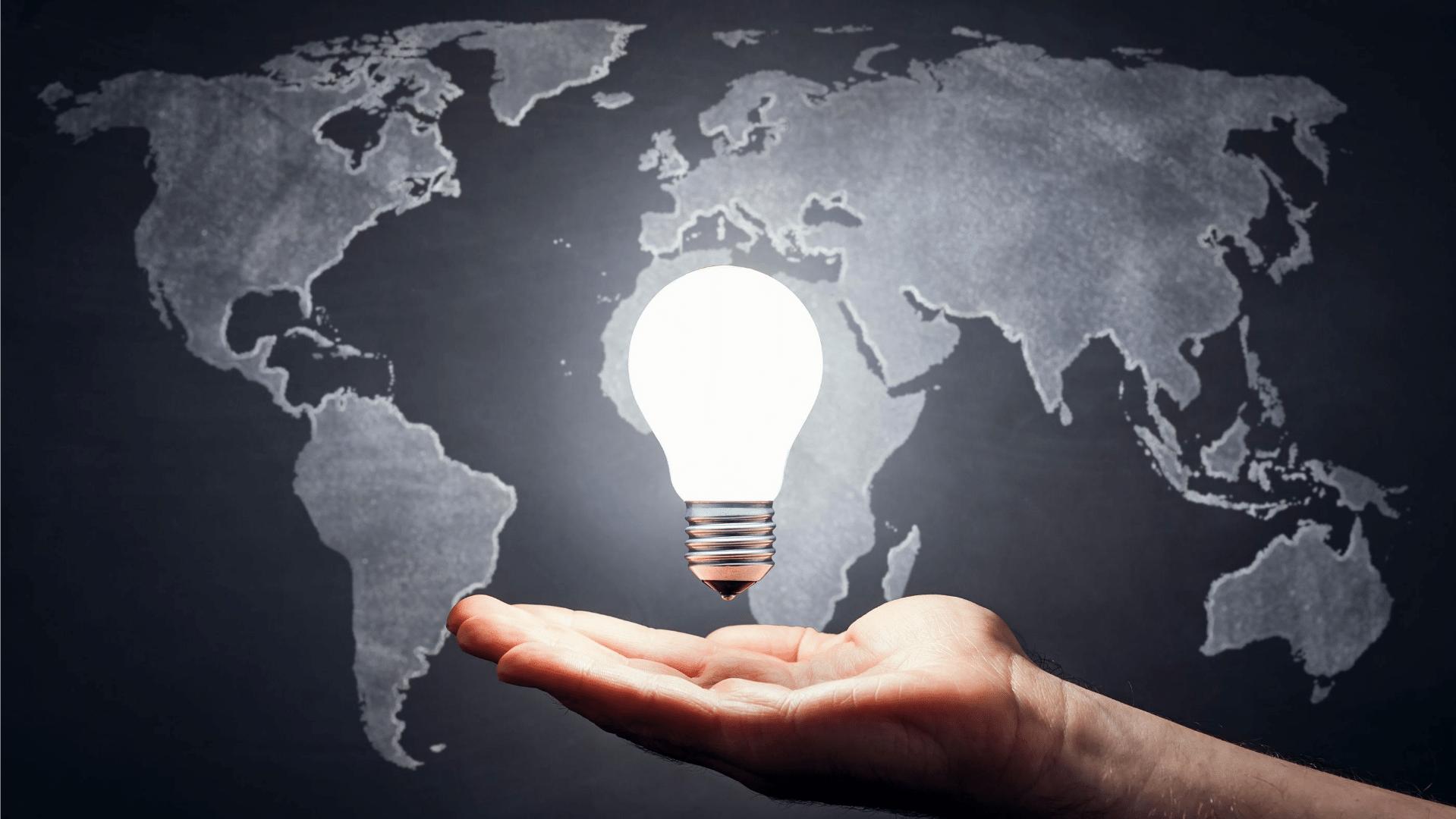 world map lit lightbulb above open palm