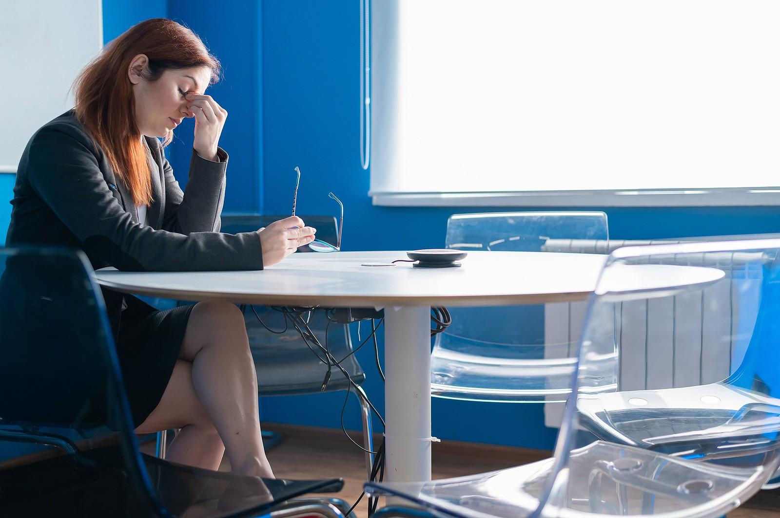 Exhausted, troubled Caucasian woman sitting in empty workshop space