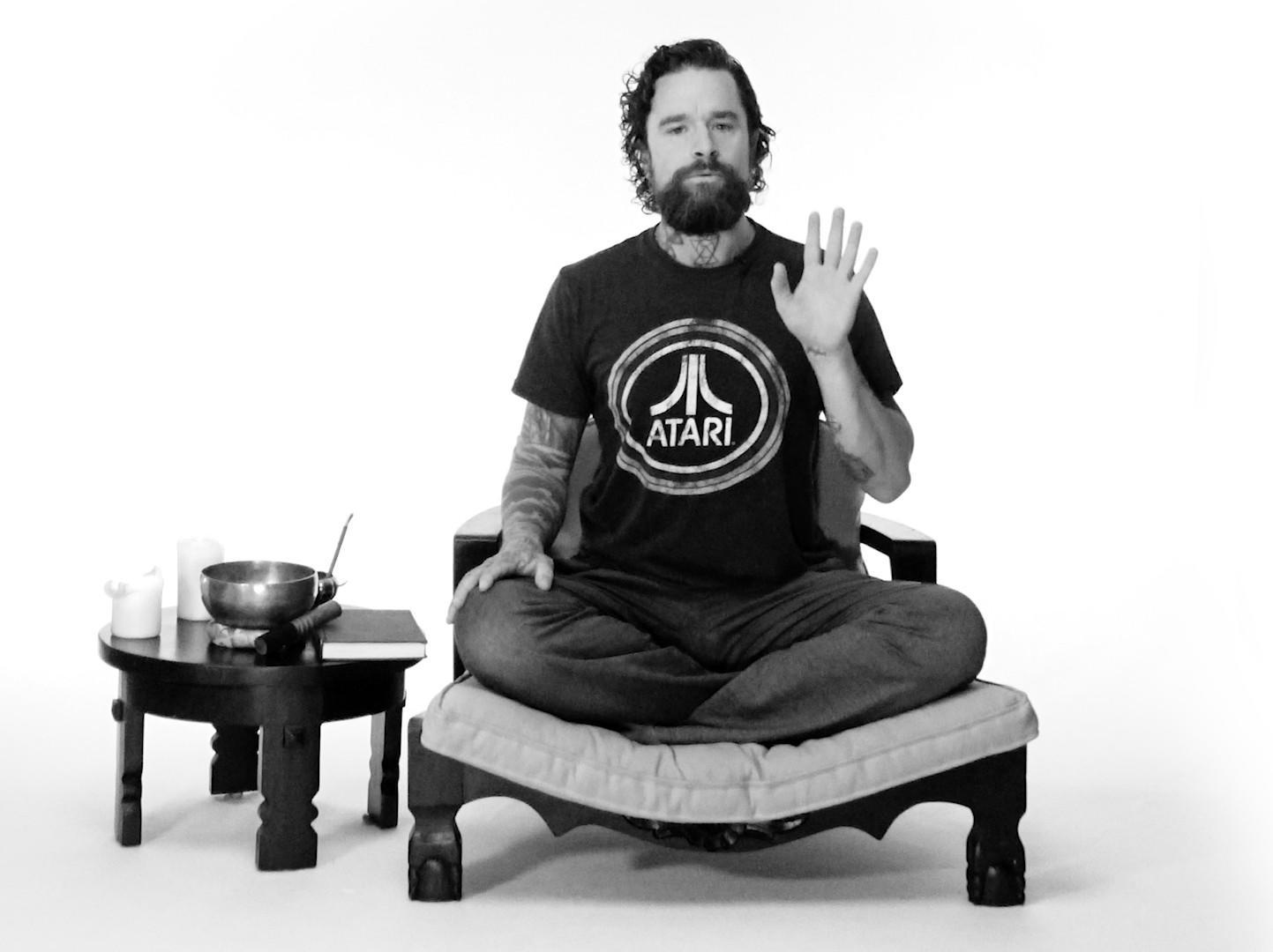 Aaron Patrick, yoga teacher, sits on a meditation chair