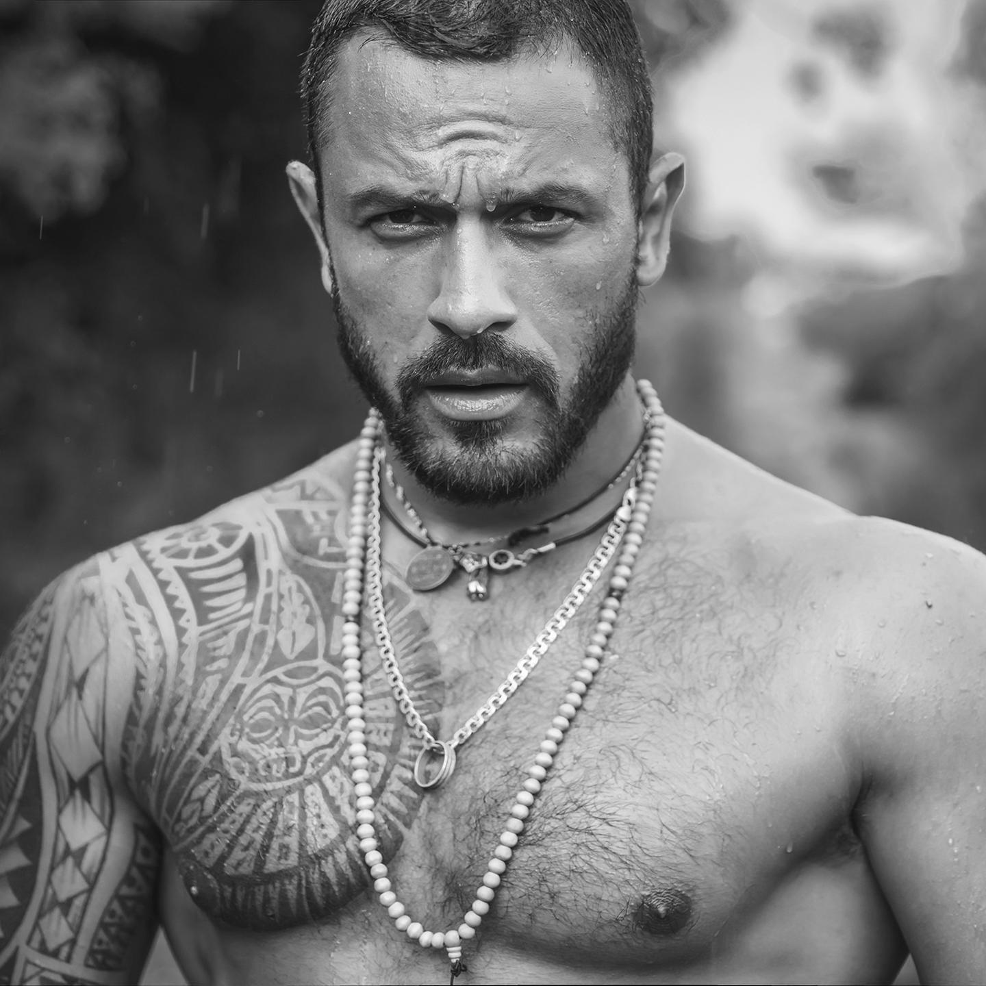 shirtless, tattooed man gazes into the camera with strength and confidence