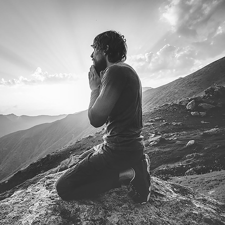 kneeling man meditates on a mountaintop