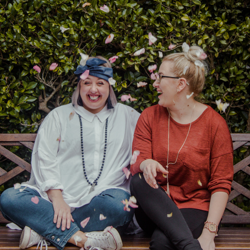 Sam and Jo, virtual assistant coaches, sitting on park bench laughing