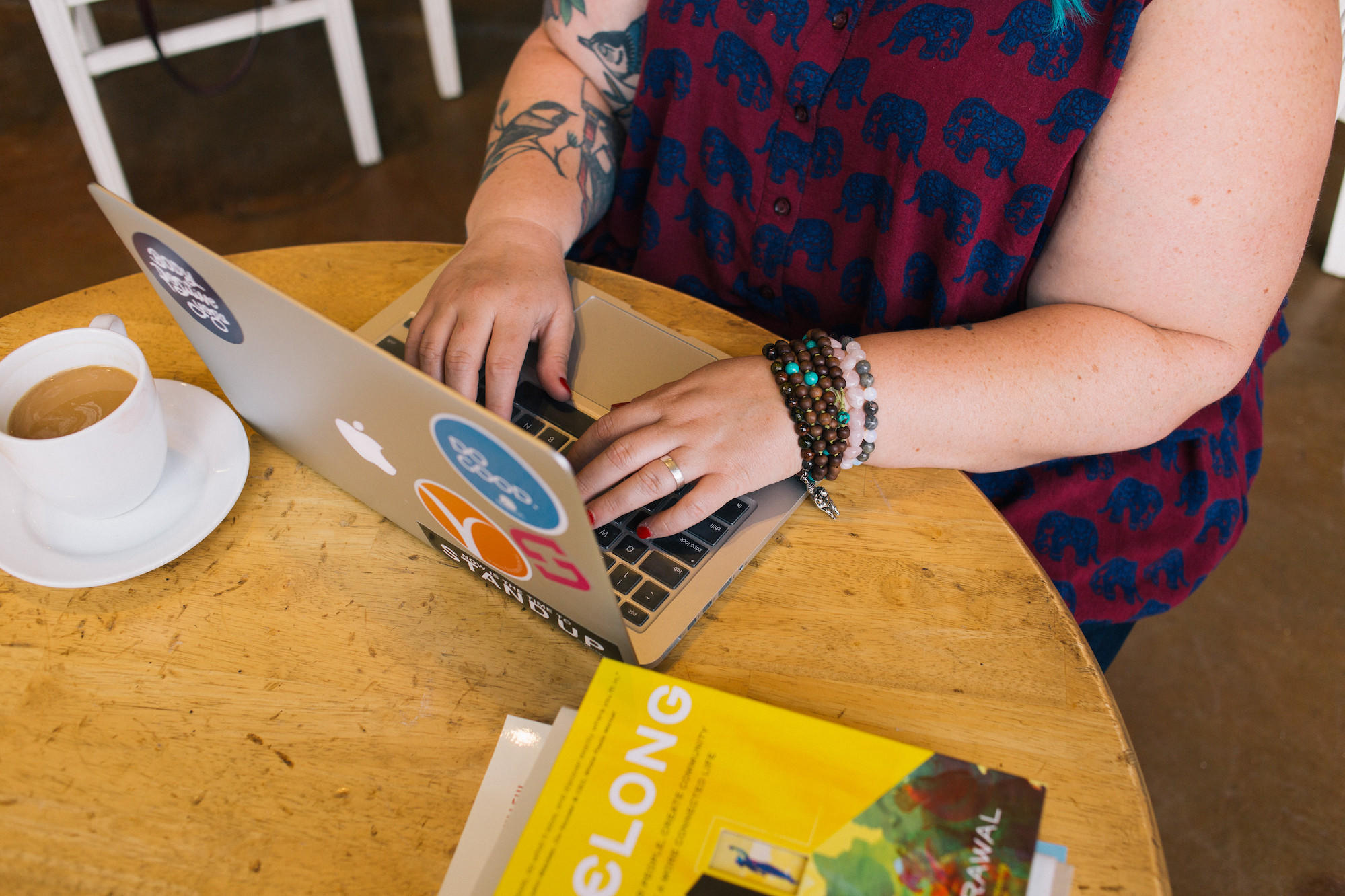 Photograph of Amber's hands typing on a laptop. A cup of coffee and stack of books are nearby