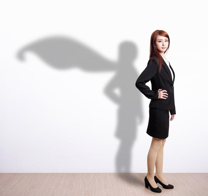 East Asian woman in business suit with a shadow in the shape of super woman