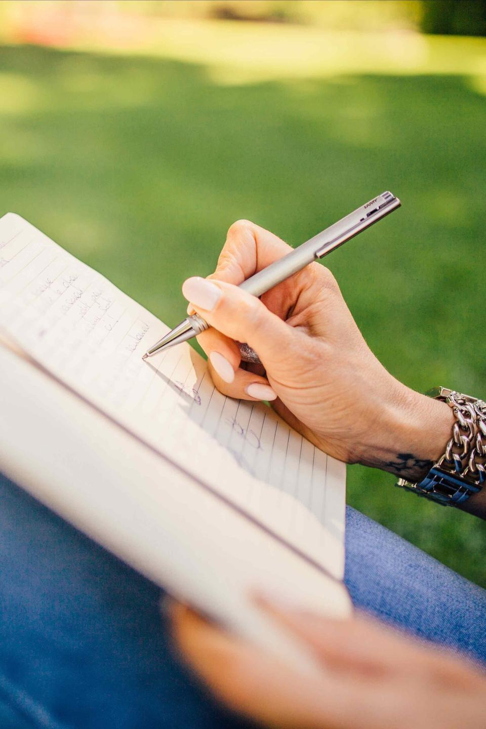 menopause woman writing in journal on grass