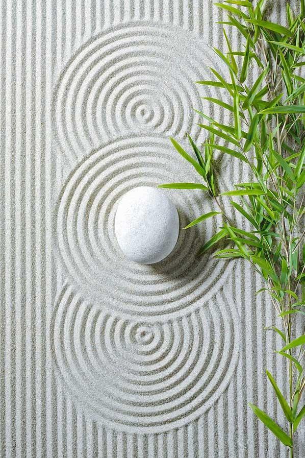 white pebble on zen swirls drawn in sand