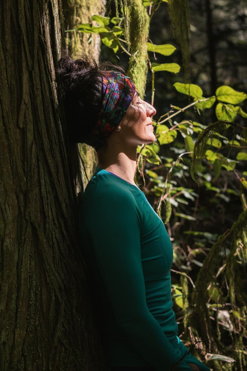 menopause woman leaning on a tree in a forest with sun rays shining on her face