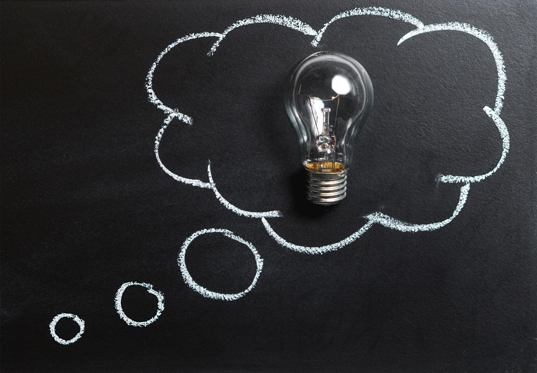 Black chalkboard drawn thought bubble lightbulb