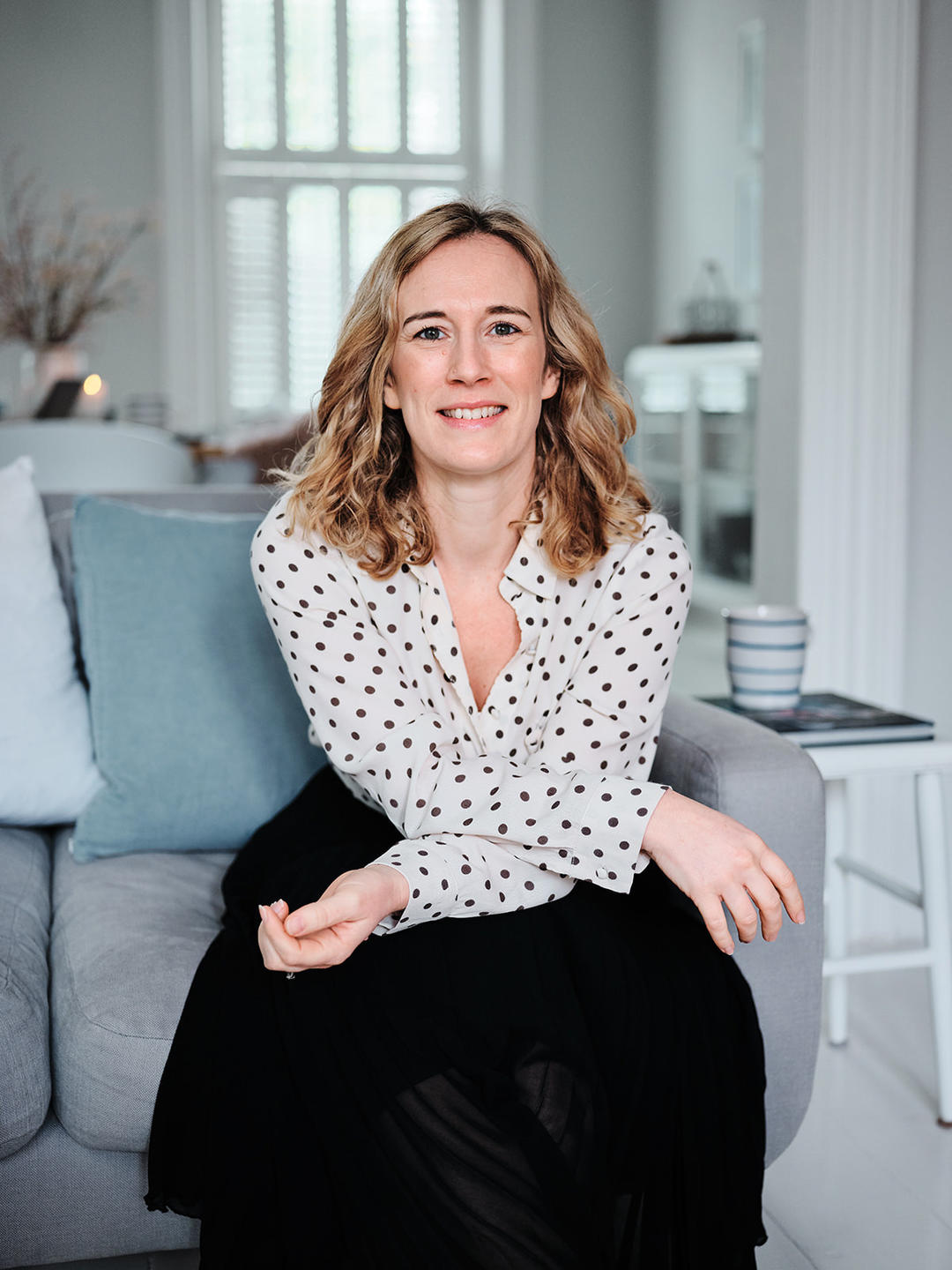 Picture of Zoe Hawkins in a spotted blouse and black skirt, sat in a chair, smiling, with her arms crossed leaning forwards