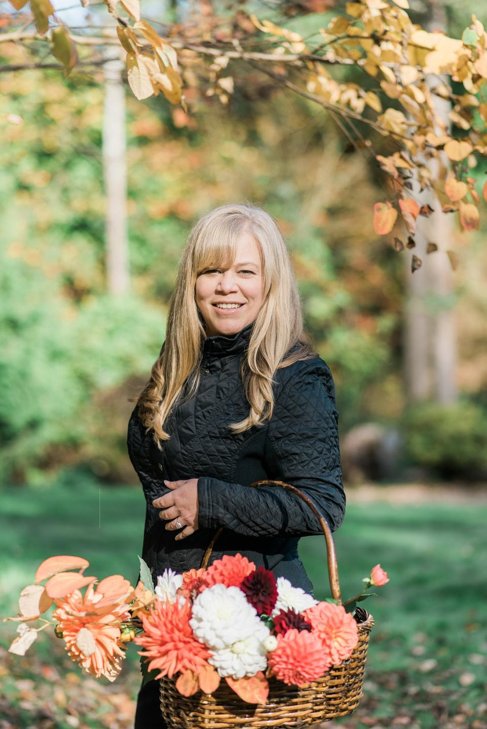 woman smiling holding a basket of dahlia flowers in the fall