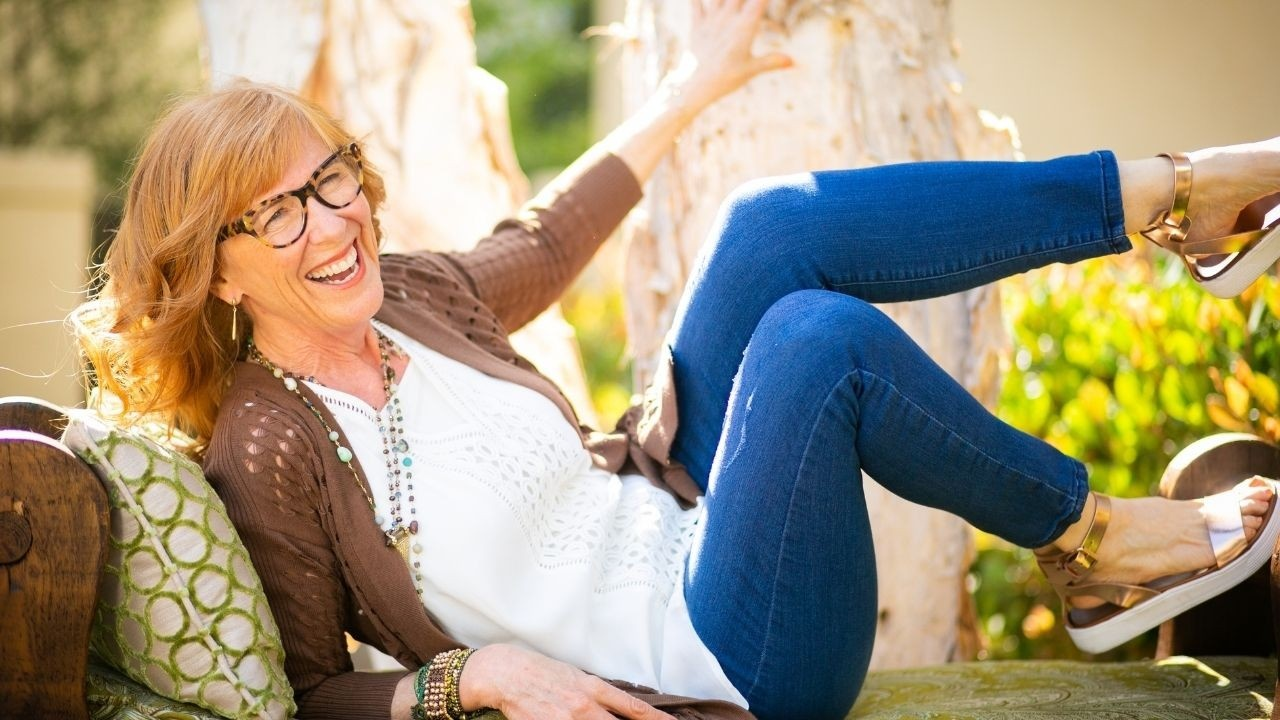 menopause coach laughing on sofa