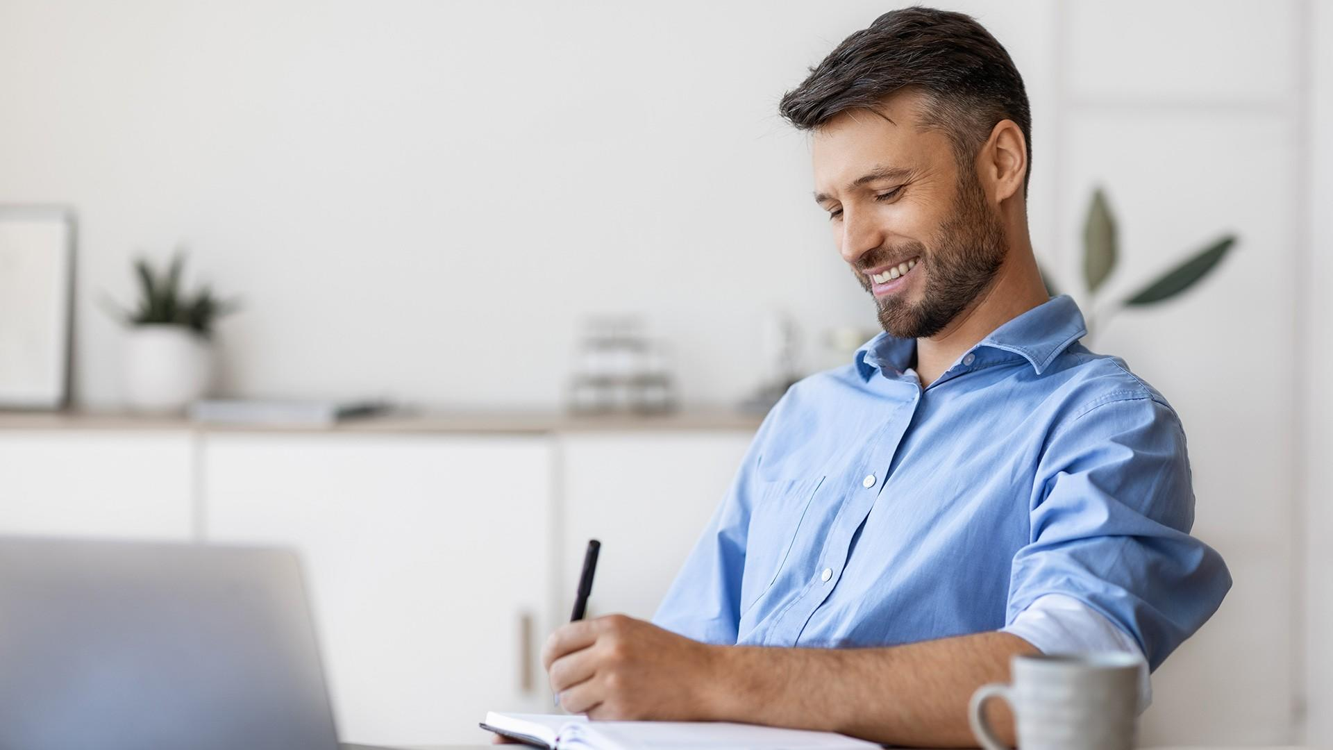 Happy Man at Desk writing in a journal