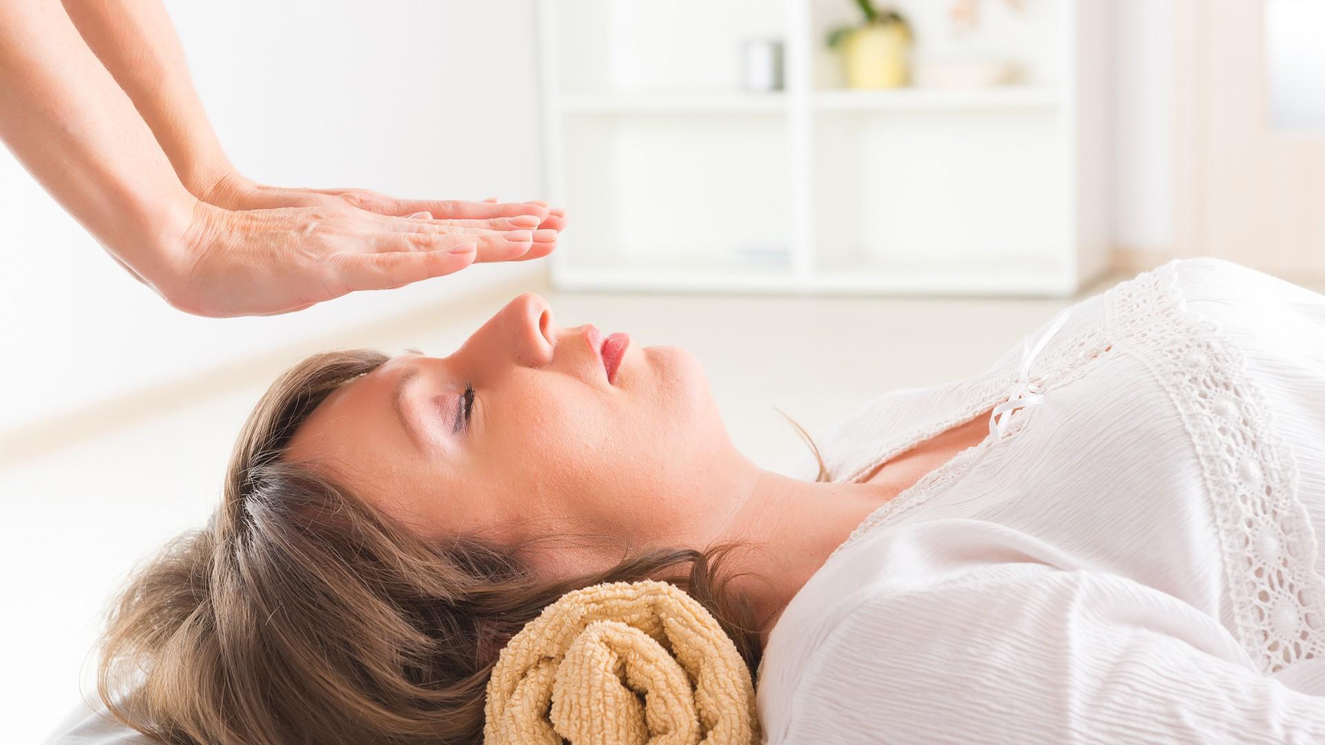 woman receiving reiki while lying down