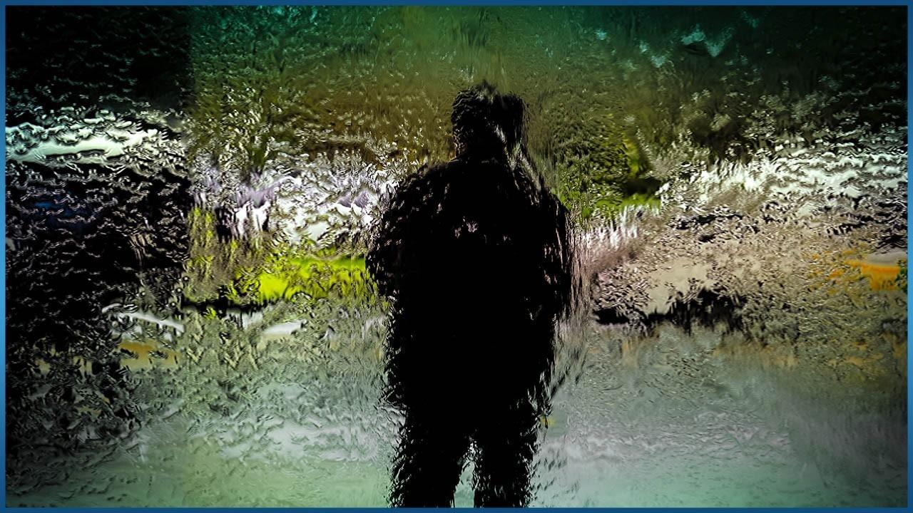 person standing behind mosaic glass
