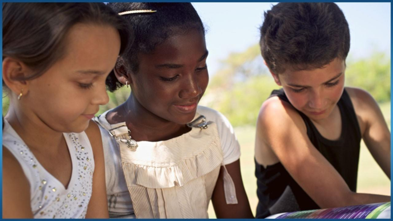 3 kids of different race reading a book