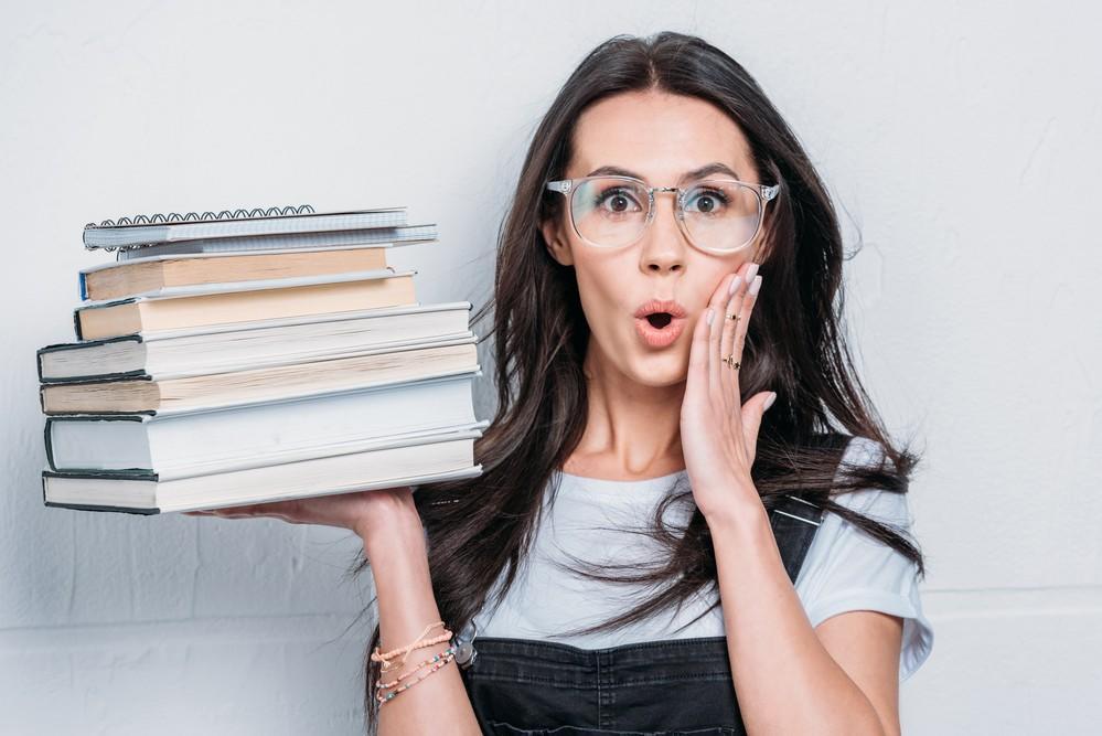 Girl Holding Pile of Profitable Books