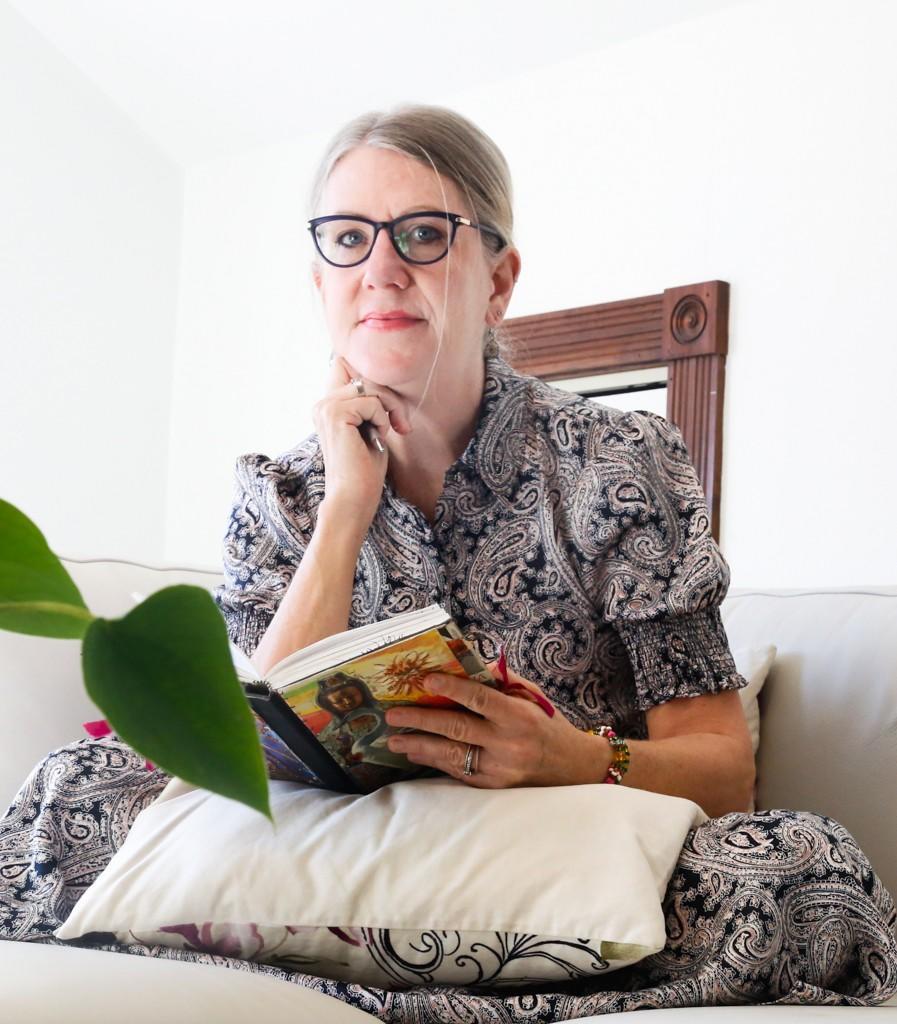 Author Rebe Huntman with handmade writing journal in writing studio
