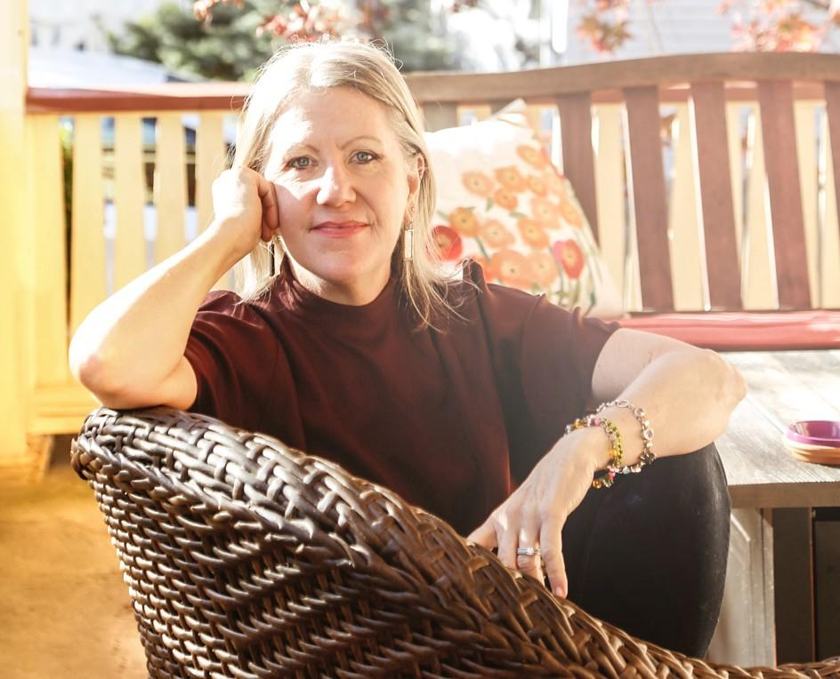 Classic author photo of Rebe Huntman sitting on front porch of writer's Delaware, Ohio home