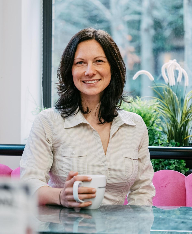 Katrin Sturm Business Coach sits at desk smiling