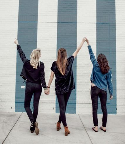 Three successful home stagers holding hands celebrating