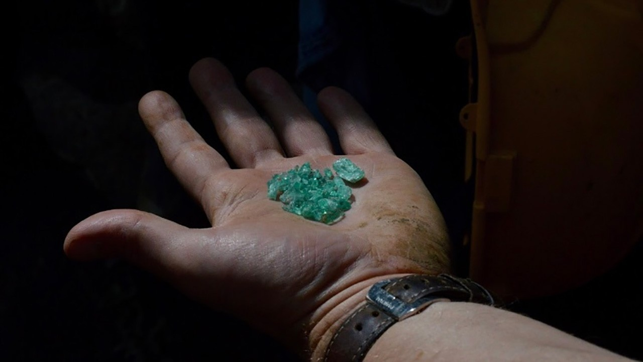 miner with rough emeralds in hand