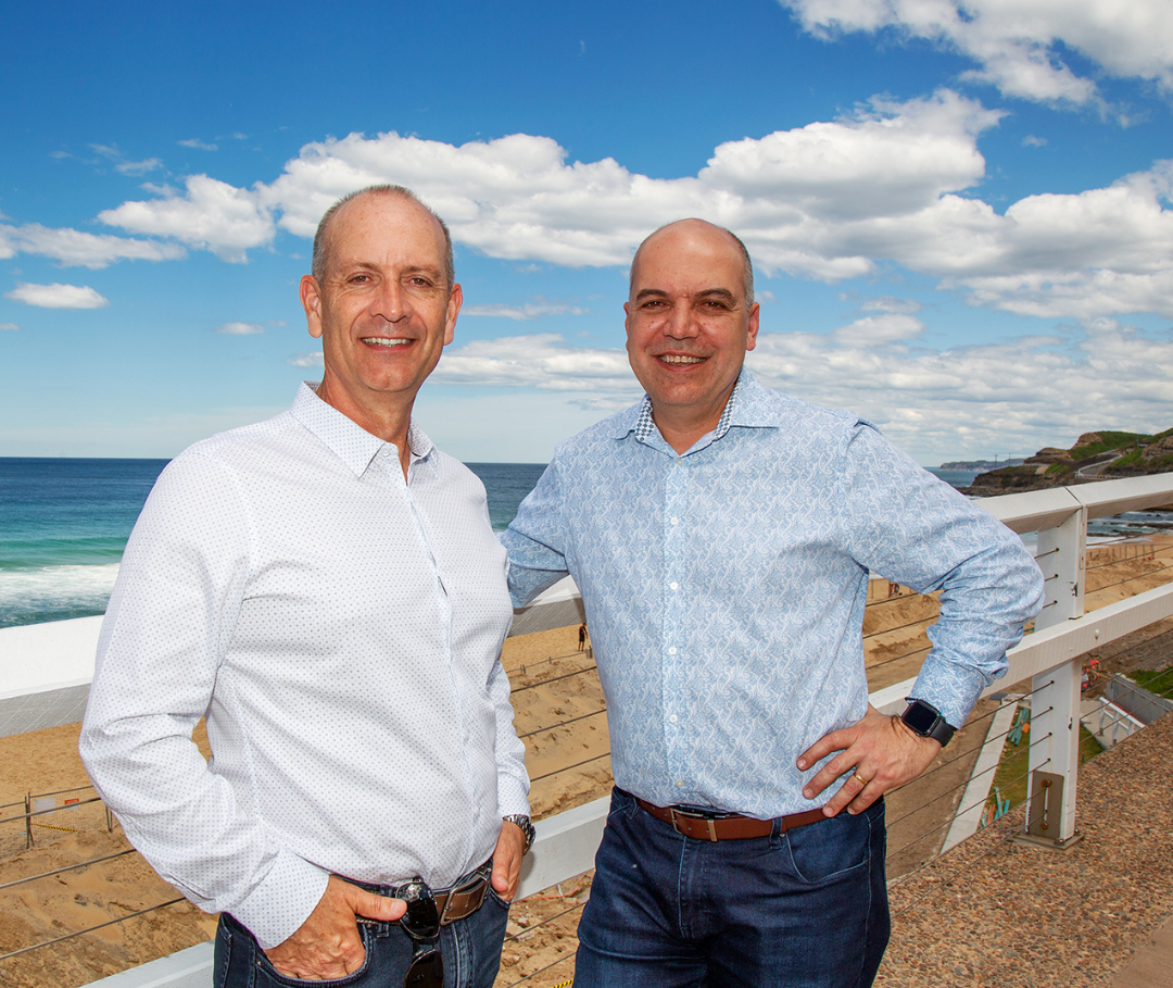 David Crook & Harry Raftos business coaches with a Newcastle beach in background