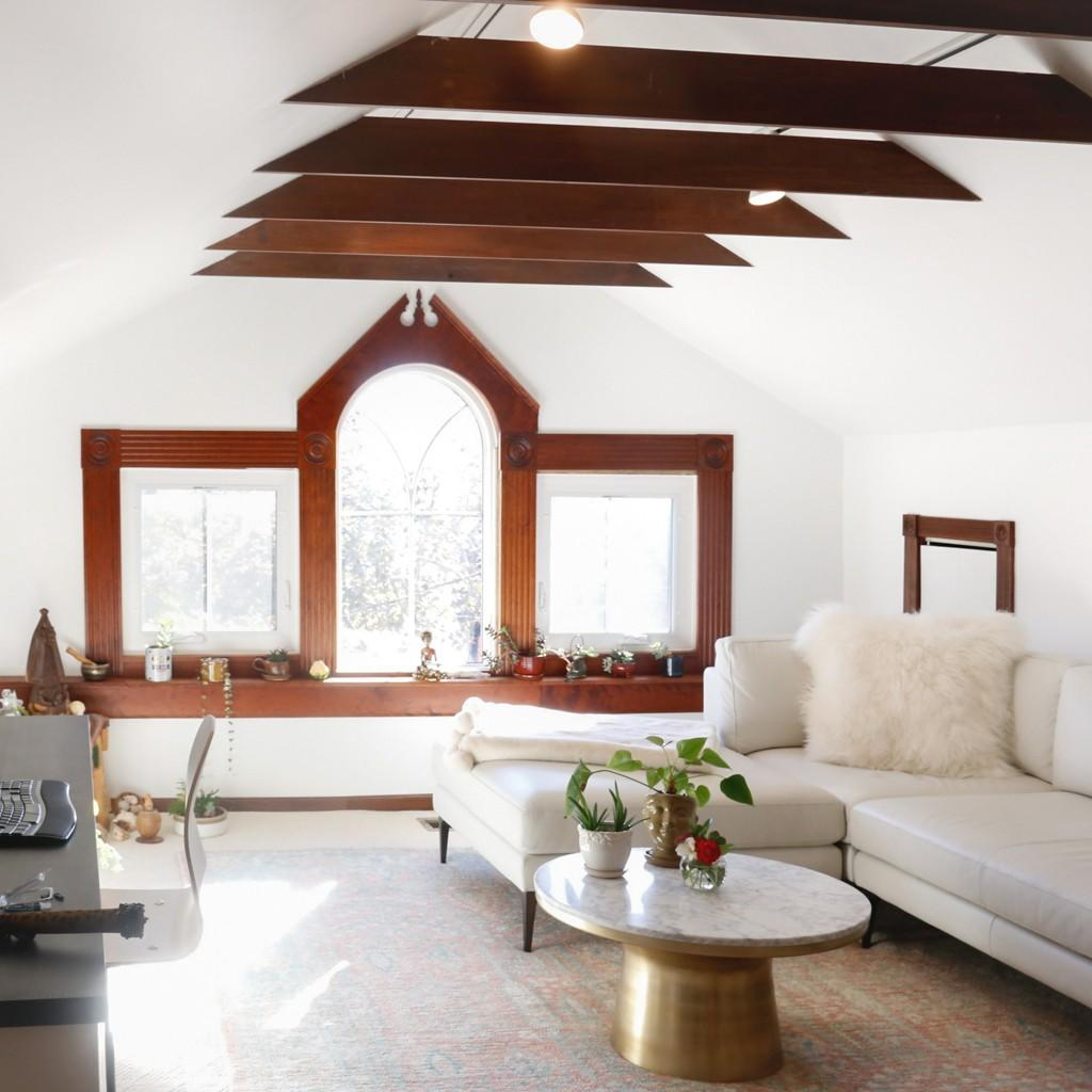 writing studio with ceiling beams, large windows, & white leather sectional