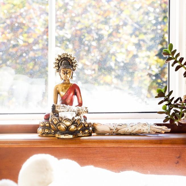 Buddha candle holder in writing studio window with succulent plant