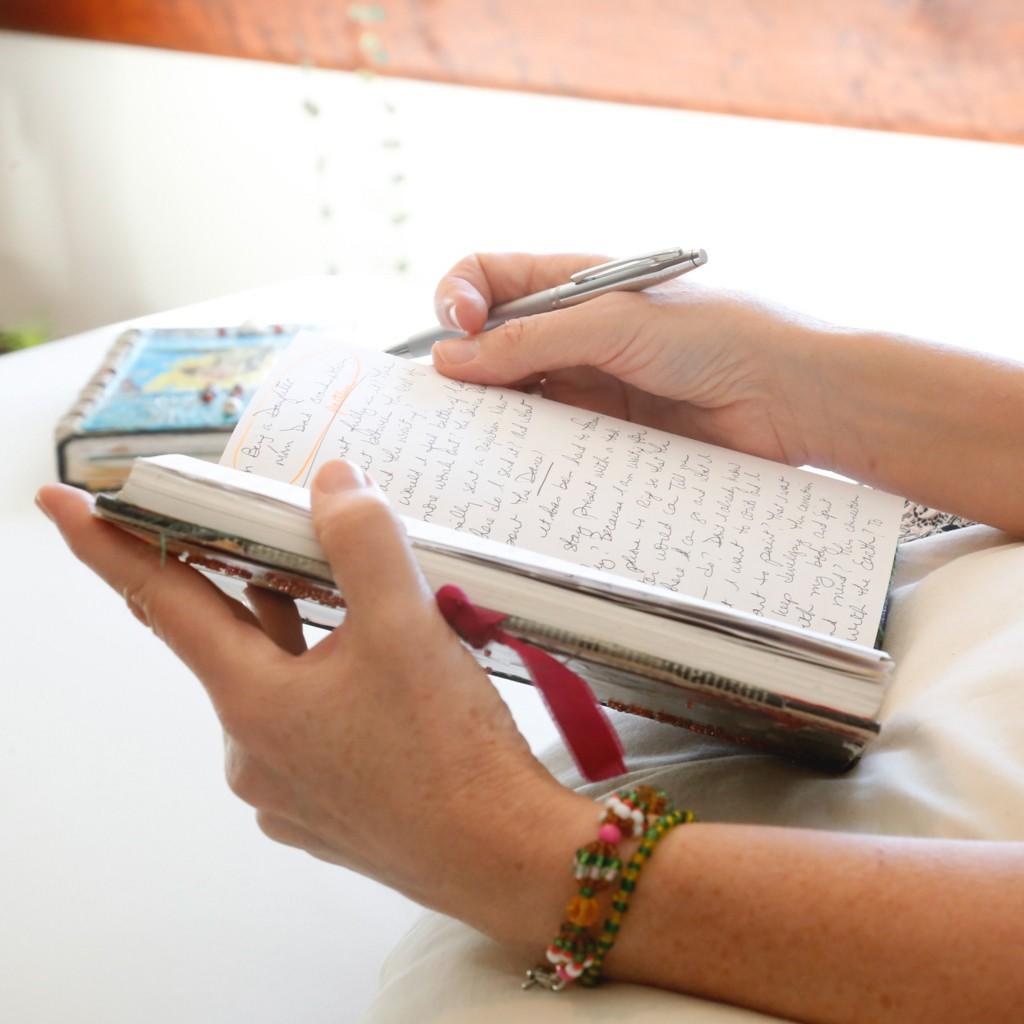 Hands of writer, author, and writing coach Rebe Huntman writing in handmade journal