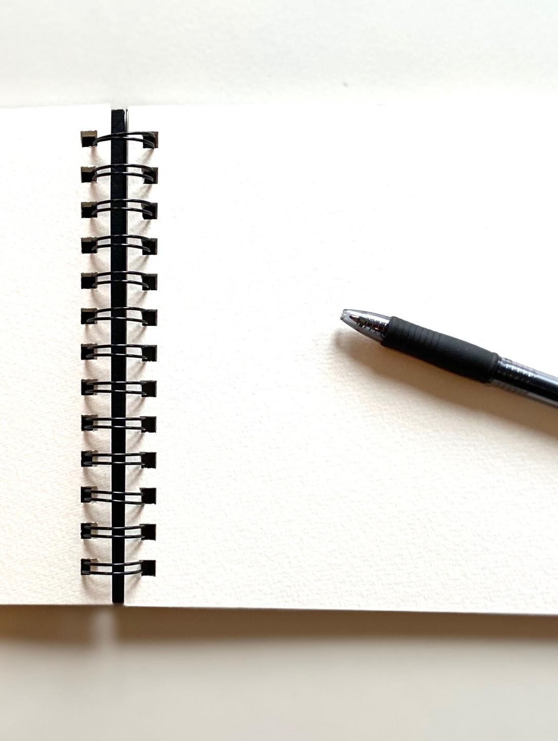 open blank writing journal with black writing pen