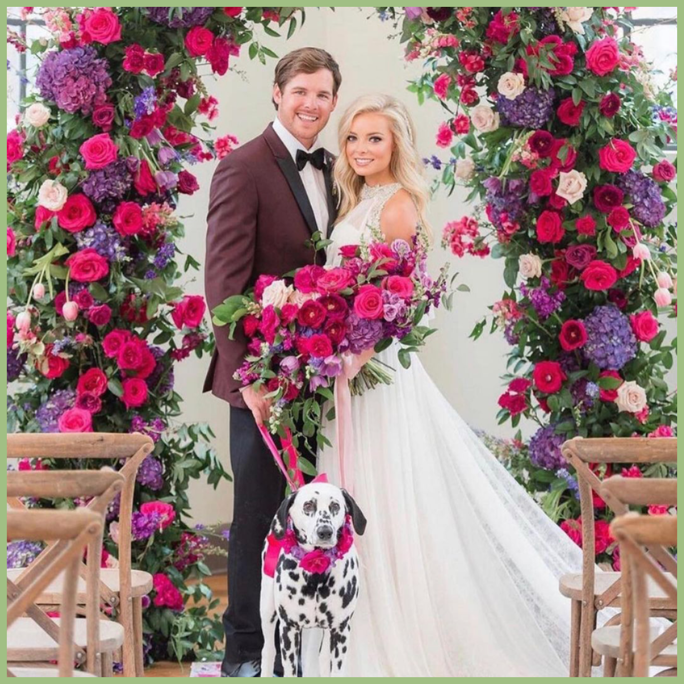 bride and groom at wedding arch with pink flowers and dog with pink flower necklace