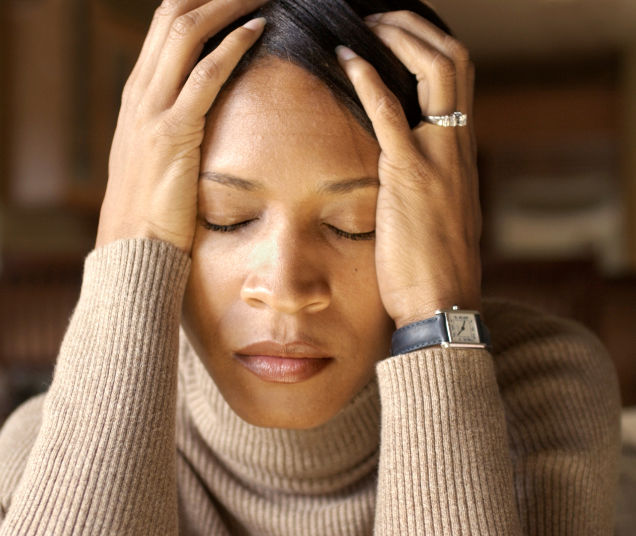 Woman with her head in her hands and eyes closed looking stressed