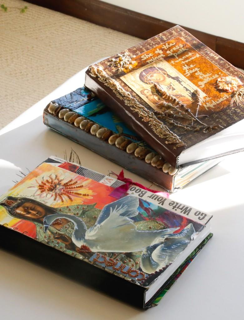 Handmade writing journals collaged with beads, paper, & images of Buddha, Mother Mary, and Ochún