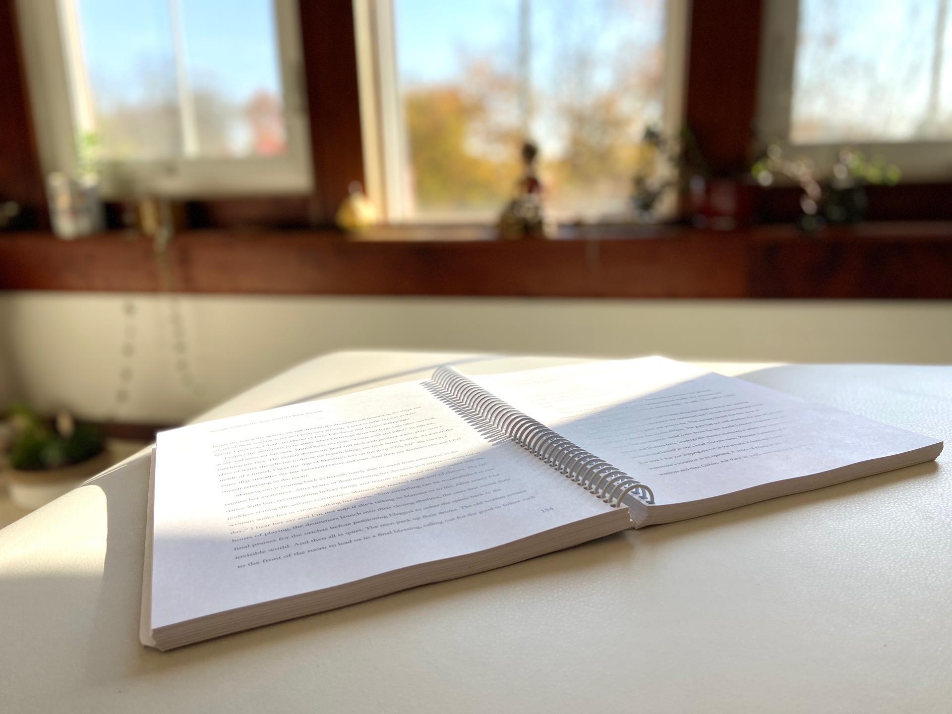 open memoir book manuscript in writing studio with window and Buddha